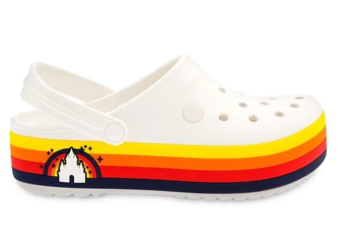 White Crocs with a yellow, orange, red, white and navy striped platform sole that also has a little Disney castle design