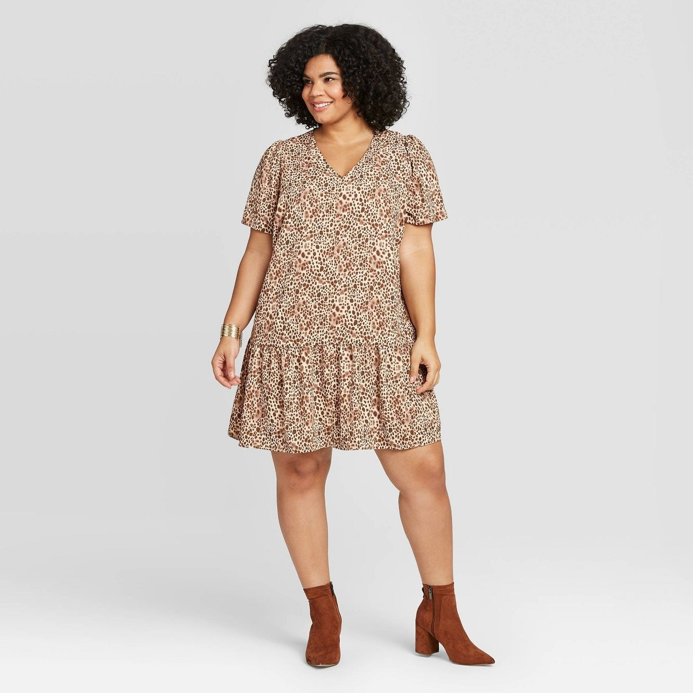 Model wearing the dress with puff sleeves, v-neck, and ruffle across the bottom hem in brown spotted print