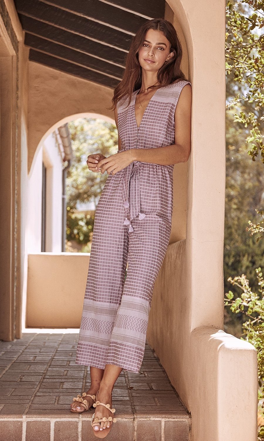 Model wearing the jumpsuit with a deep v-neck with buttons below it, tie waist, and wide legs that go to mid-calf in a pink with a graphic print