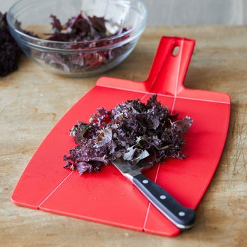 A still image shows the cutting board flat on a table with chopped vegetables on top