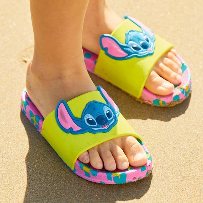 A kid's feet wearing the sandals, which have pink, blue, and yellow leopard print soles with yellow/green bands with Stitch's 3D face on them