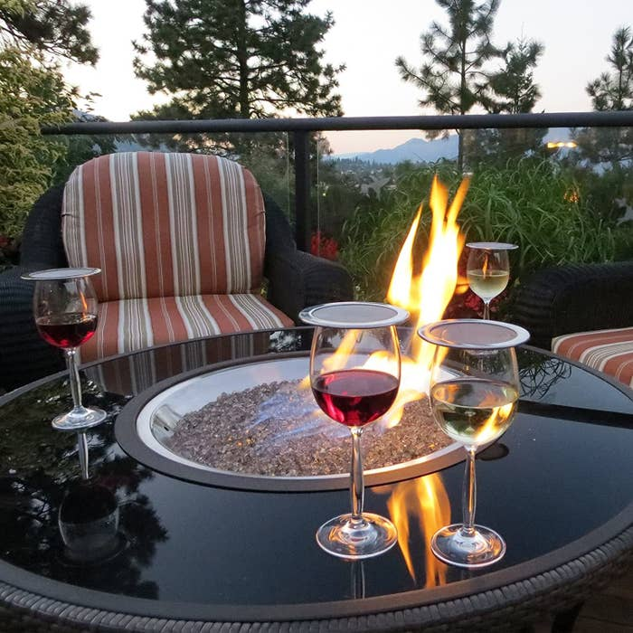 Four wine glasses on an outdoor table with wine guards on top of them