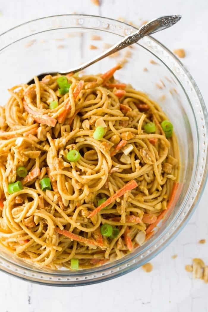 Spaghetti noodles with scallions and carrots in a creamy peanut sauce with chopped peanuts