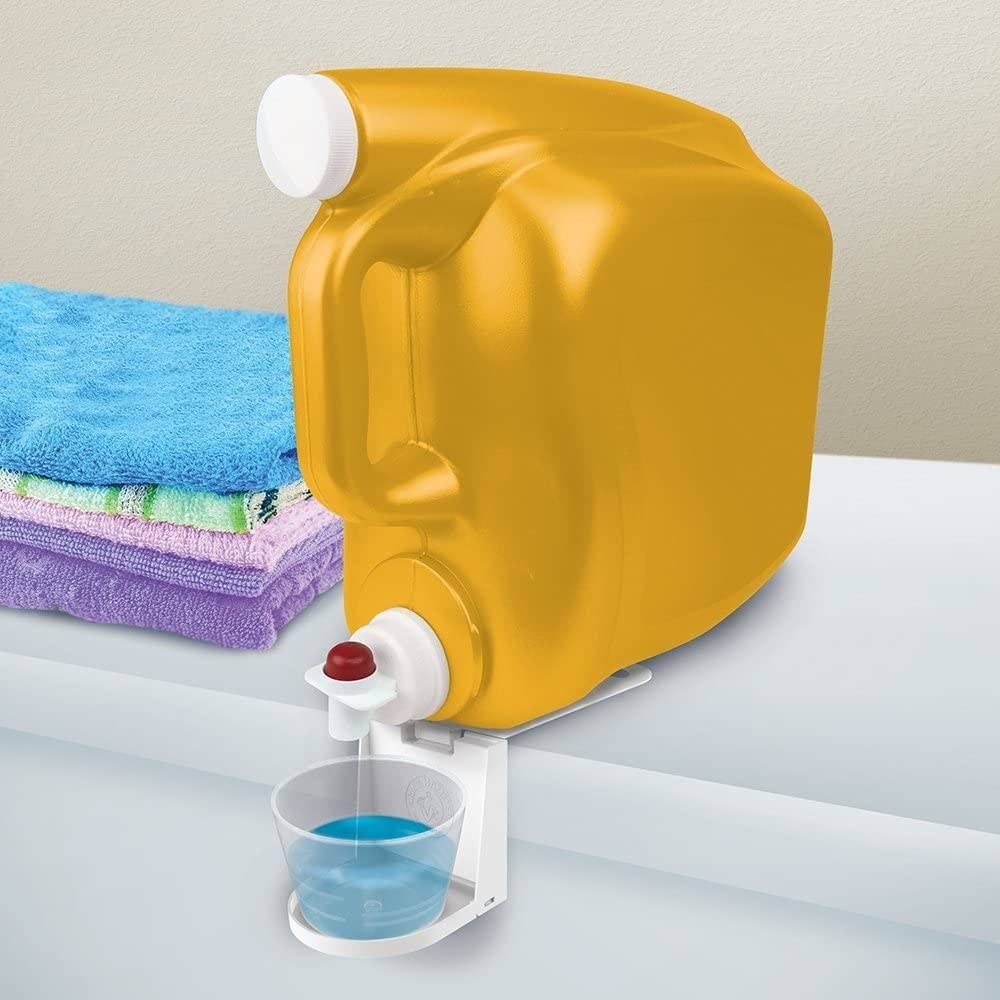 A detergent cup sitting on the cup caddy being filled with detergent from a large bottle