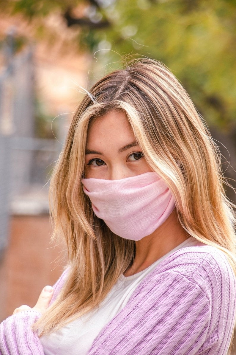 A model in a pale pink face mask