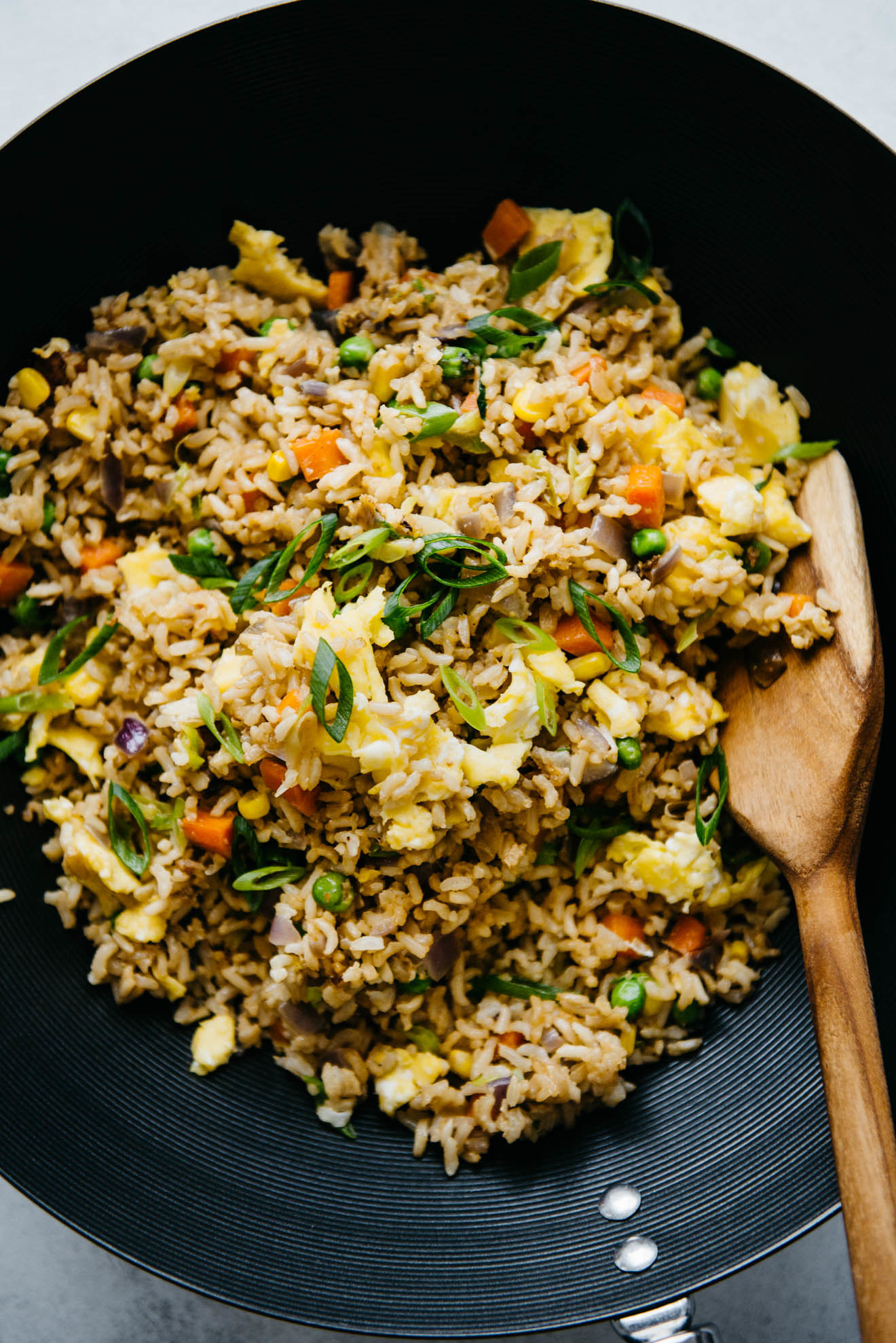 A skillet with egg fried rice and mixed veggies like carrots, peas, and scallions