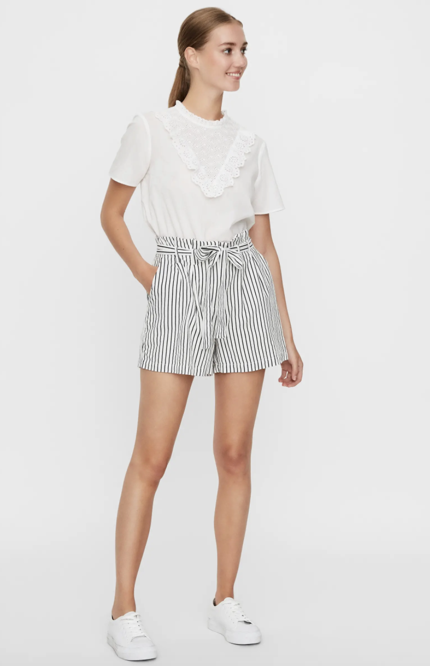 Model wearing the shorts with a tie around the waist with their hand in the pocket in white with black stripes