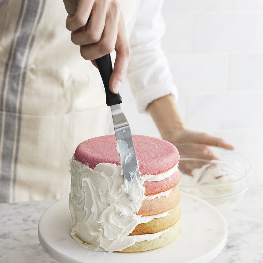 A person using the spatula to frost the side of a cake