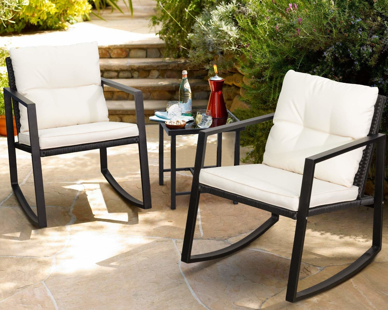 A set of two black-framed outdoor rocking chairs with white cushions