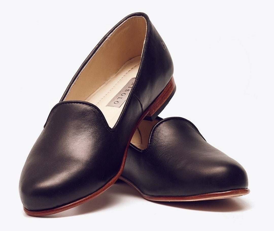 pair of black leather smoking slipper flats with rich brown bases