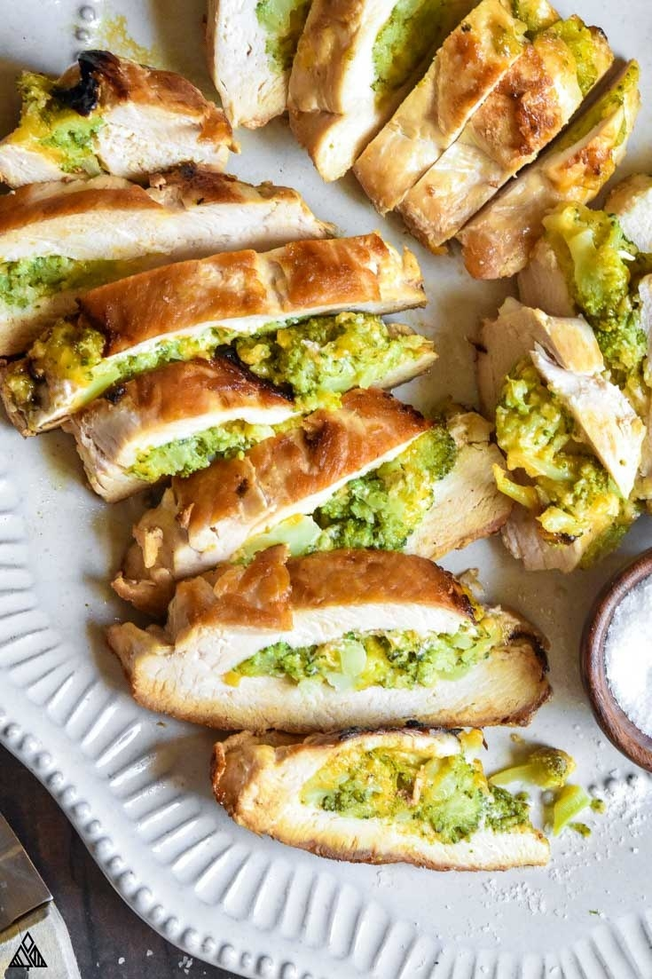 Sliced chicken breast filled with cheesy broccoli on a plate