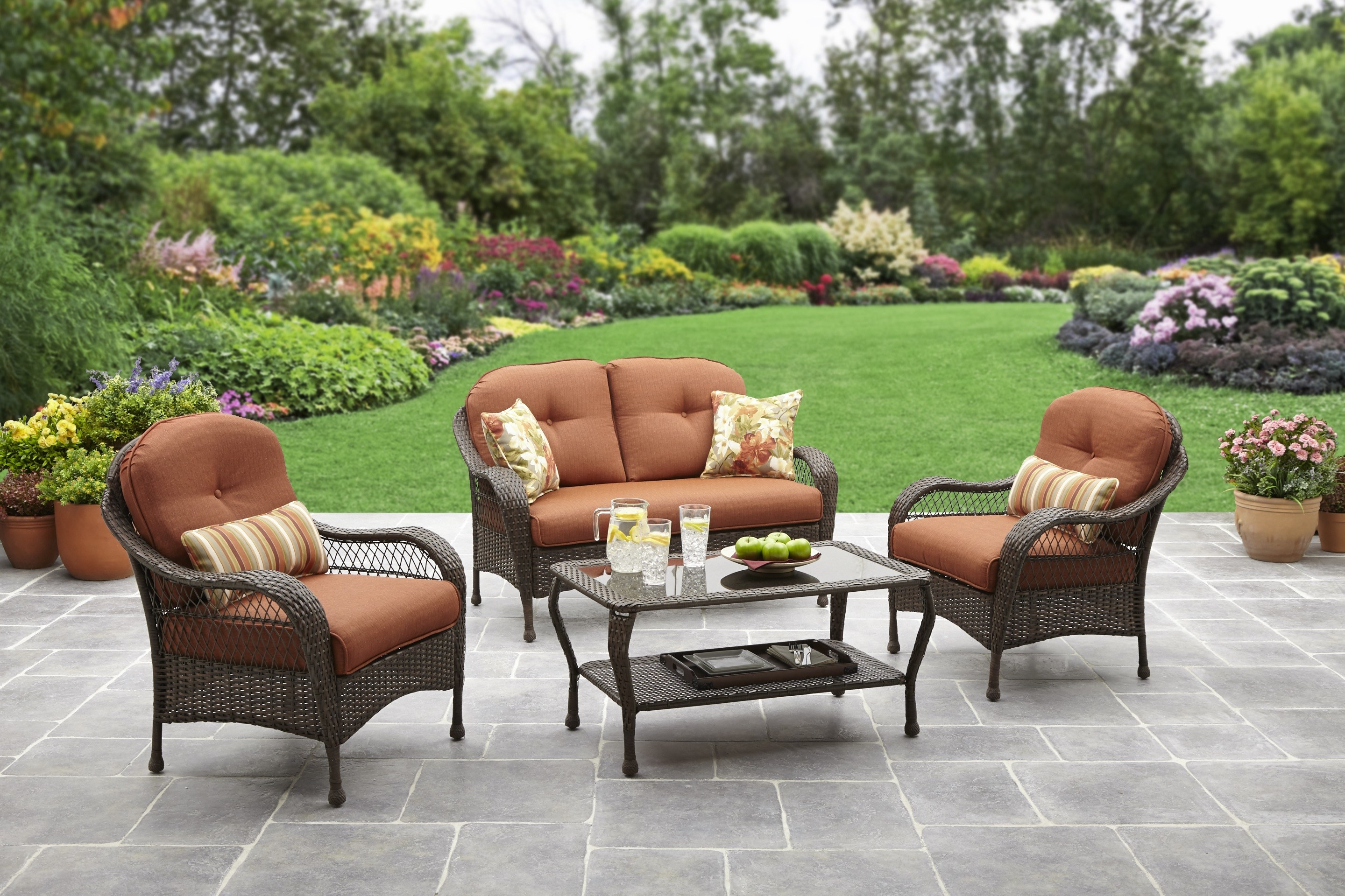 A dark brown wicker, outdoor set including a two-level table, two chairs, and one love seat