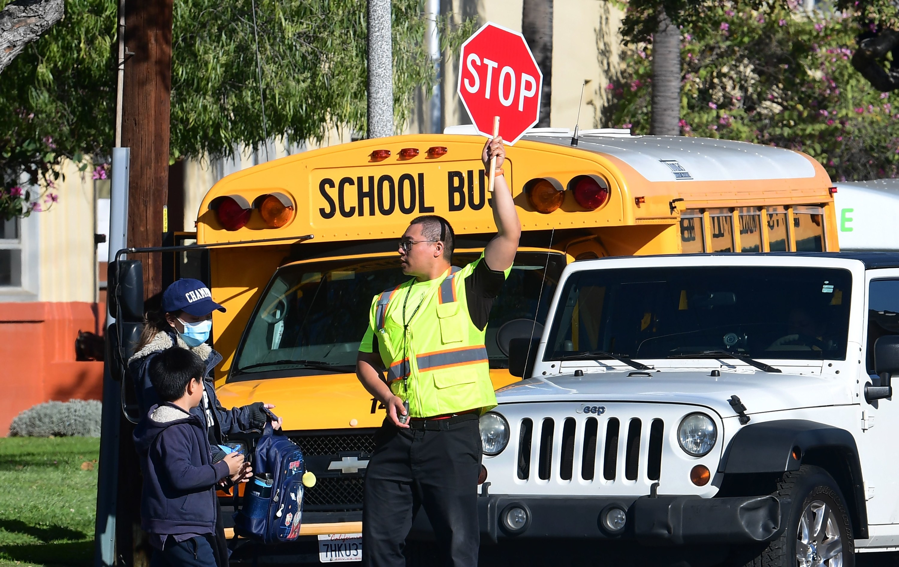 A crossing guard stops traffic in front of a school bus