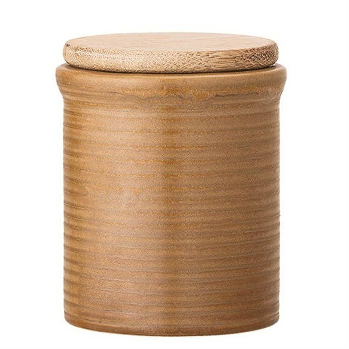A cylindrical shaped canister with a ribbed siding and a wood lid
