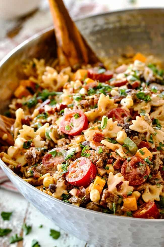 A bowl of cowboy pasta salad with bow tie noodles, ground meat, cheese chunks, cherry tomatoes, and herbs in a creamy dressing