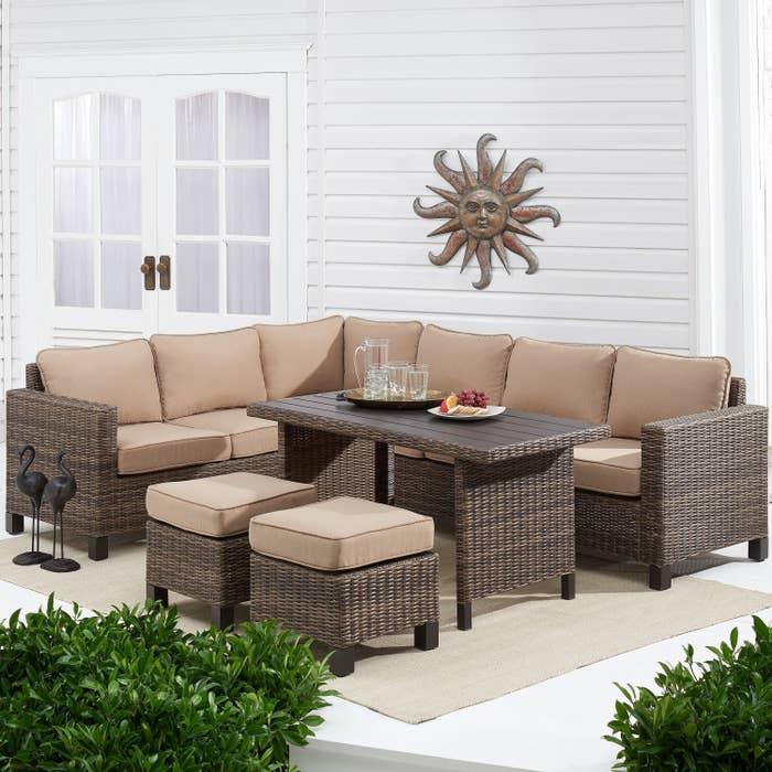 Dark brown wicker table, ottomans, and sectional couch with light brown cushions