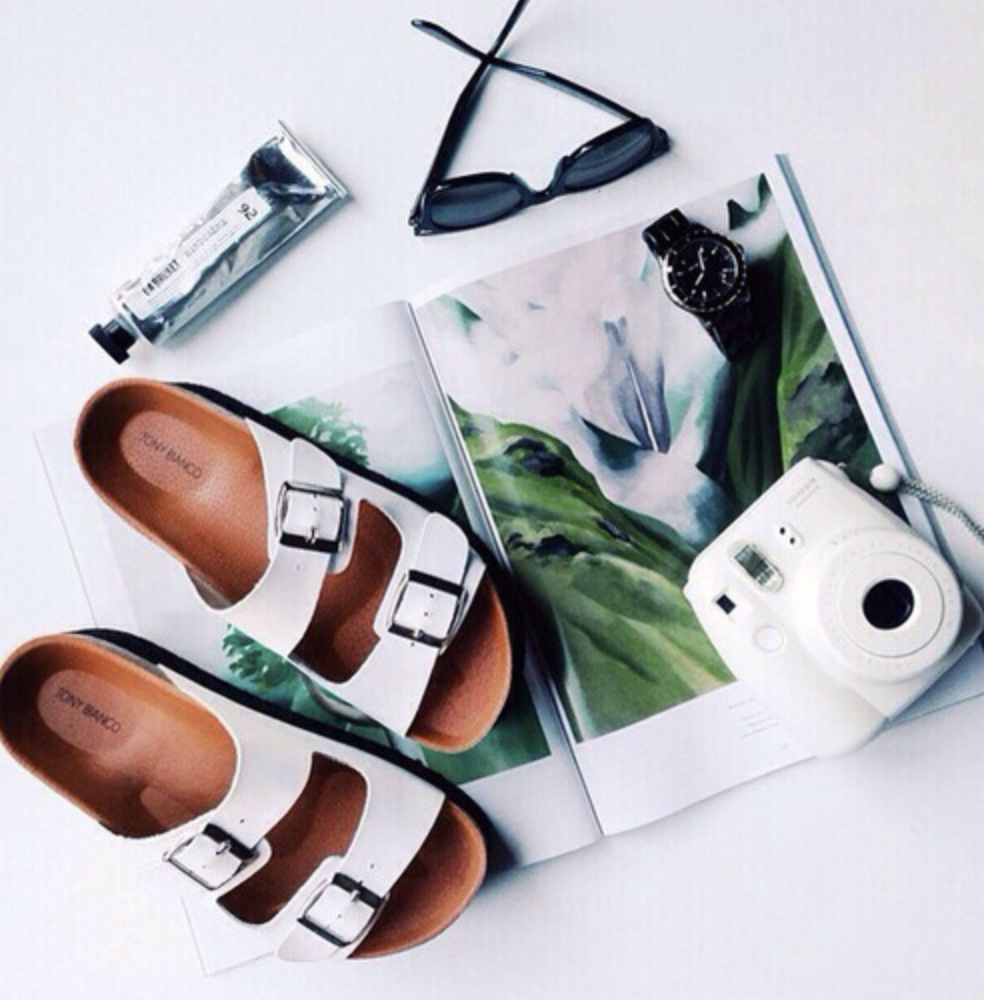 Polaroid camera on top of a magazine next to sandals