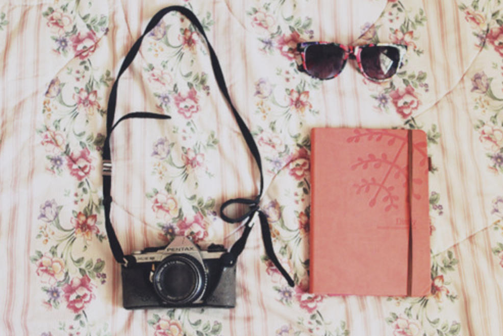 Top down photo of camera, journal, and sunglasses