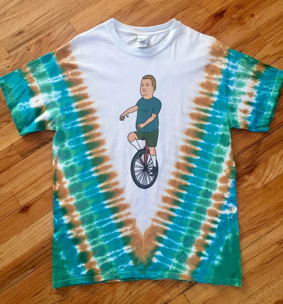 "shirt with Bobby from ""King of the Hill"" riding a unicycle with white background and green and brown tie-dye pattern"