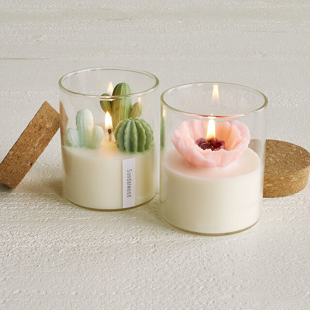 A white candle with detailed peony and cactus made out of wax