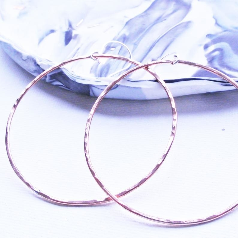 large copper tone hammered texture hoop earrings learning against a marble print jewelry dish