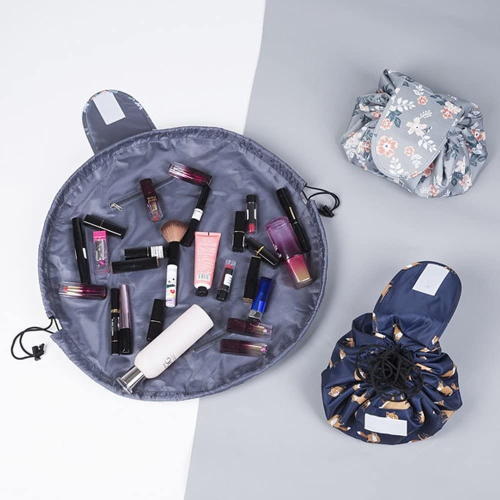 A small makeup bag with a drawstring that spreads out like a blanket There are tons of makeup products on top of it