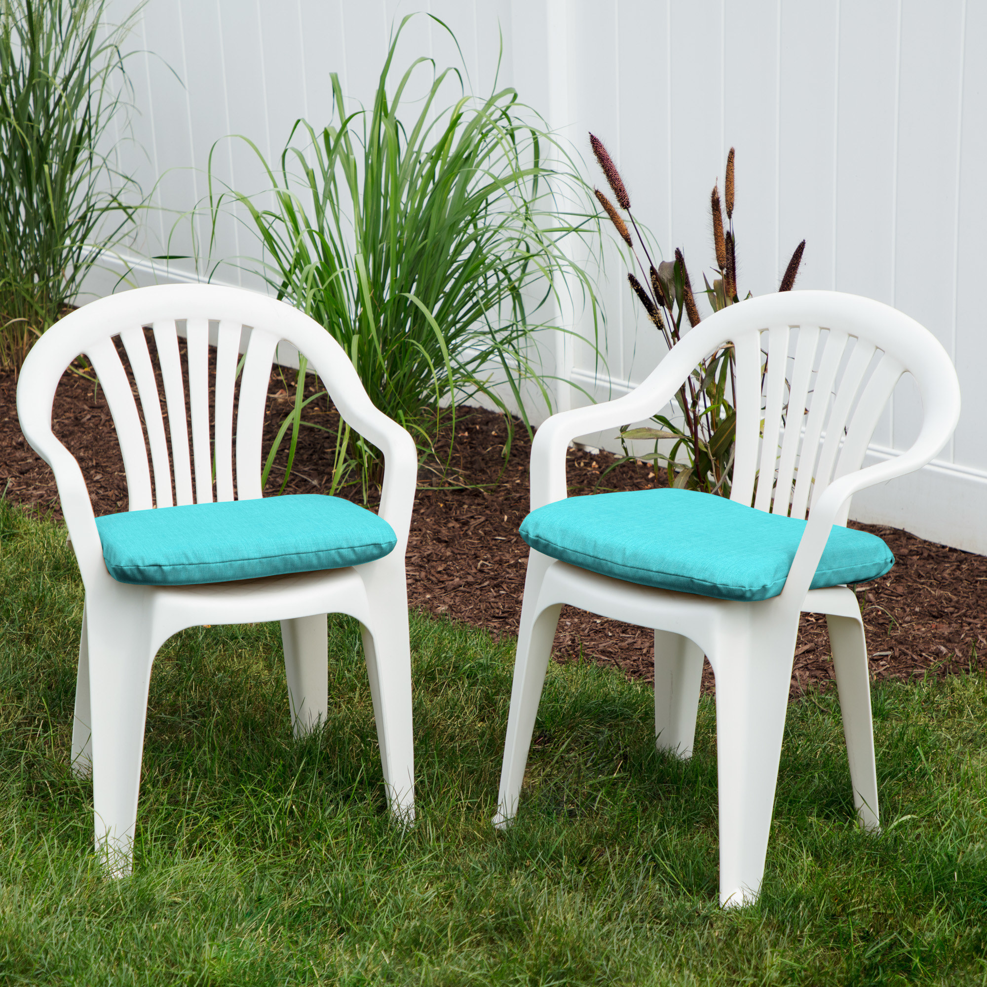 Two white, plastic patio seats with aqua color cushions