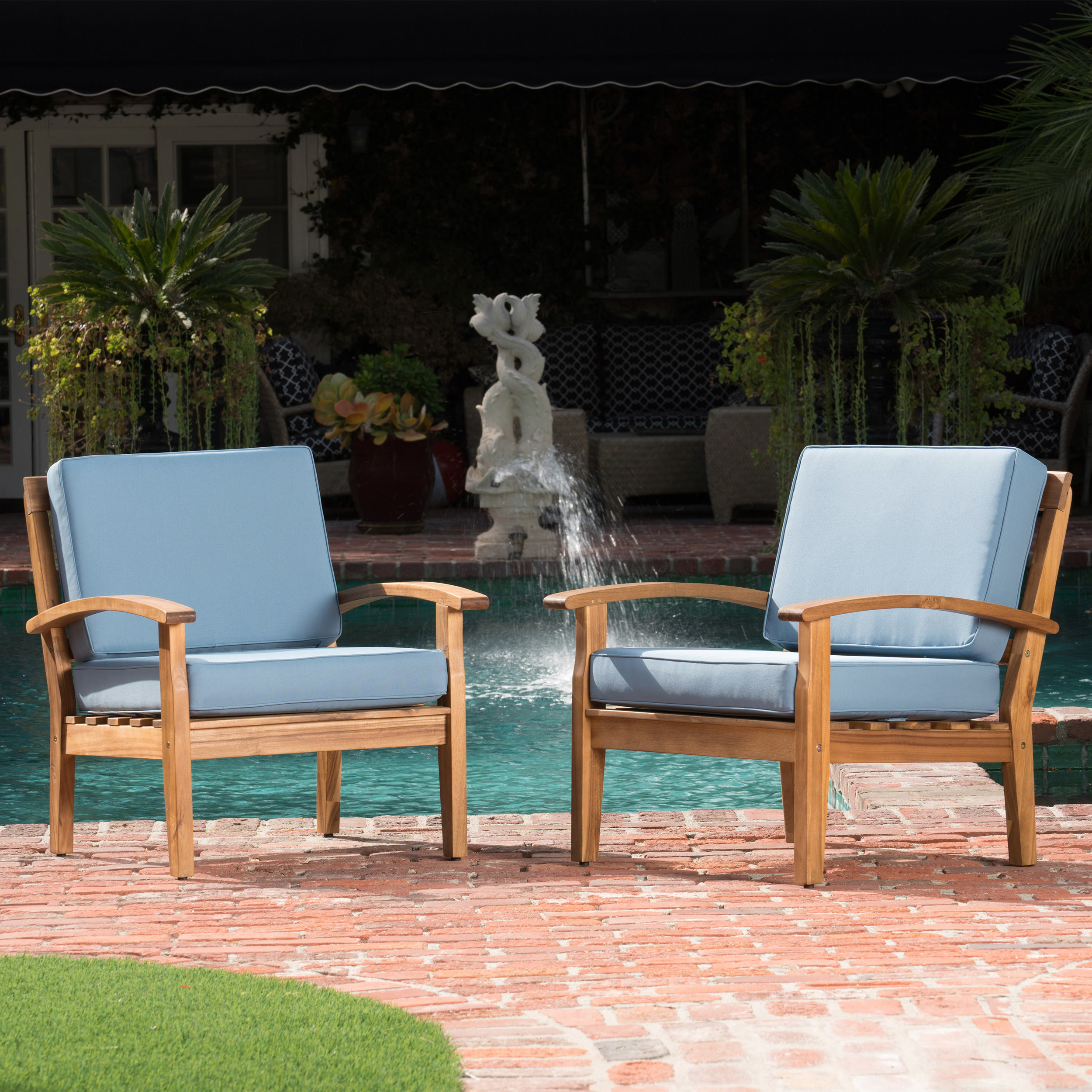 Two wood-framed outdoor chairs with light blue cushions