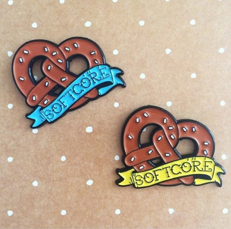 "two enamel pins in the shape of a large soft pretzel with ""softcore"" on a banner across it"