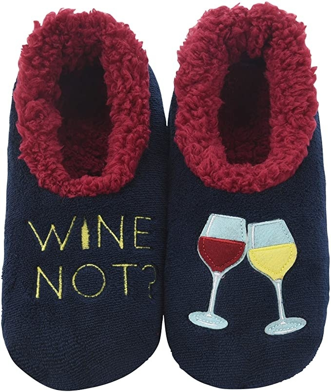 One slipper says wine not and the  other has a glass of red and white wine clinking