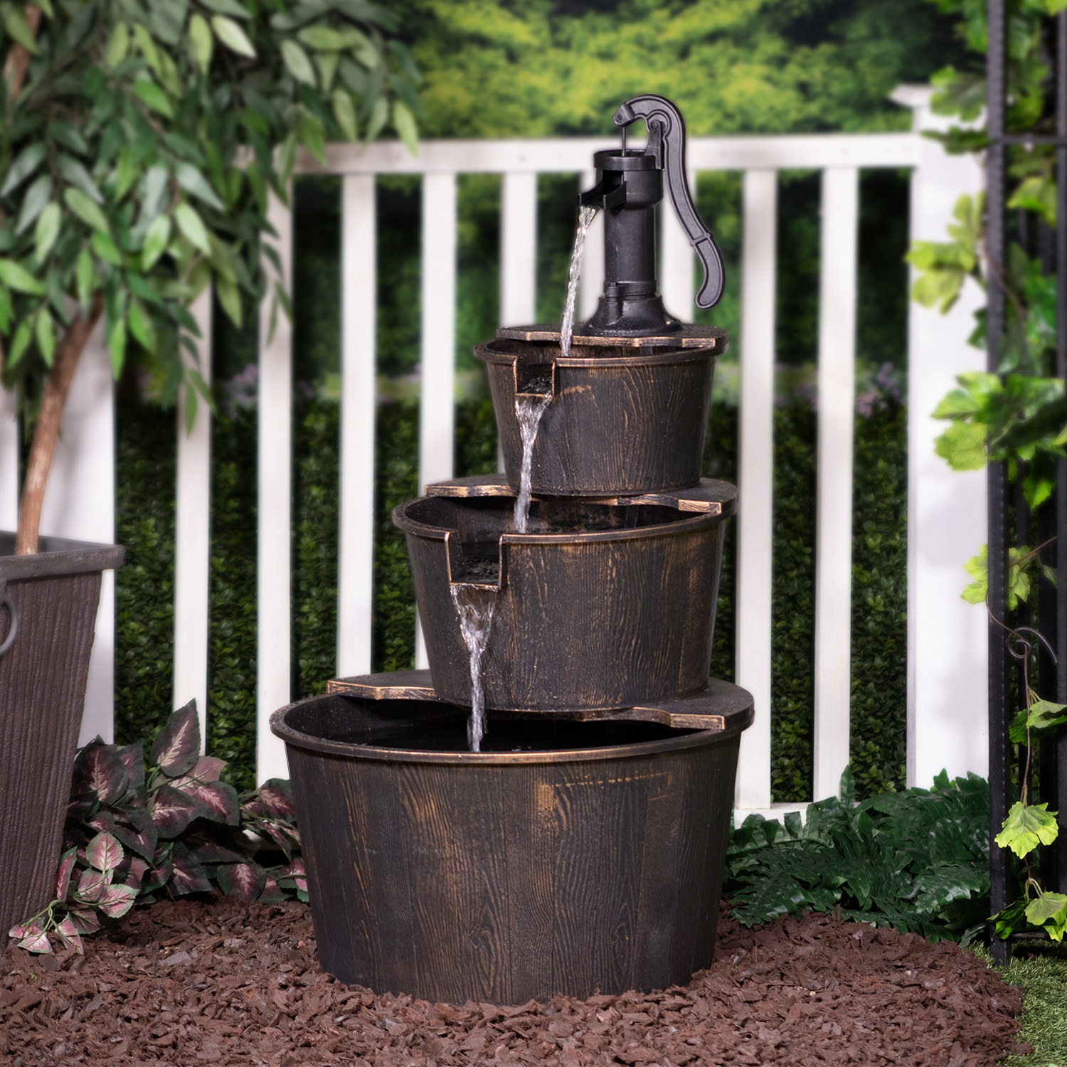 A three-tier, rusted pump fountain with water running into each basin