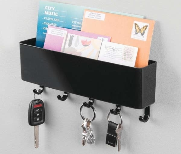 A black organizer hanging on the wall filled with envelopes, featuring five hooks on the bottom holding onto keys
