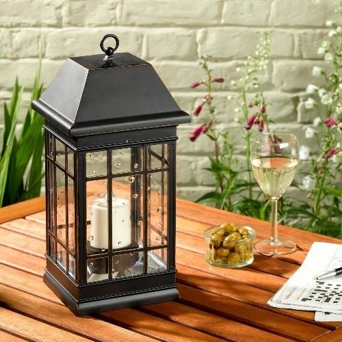 A square black solar lantern with clear panes for light