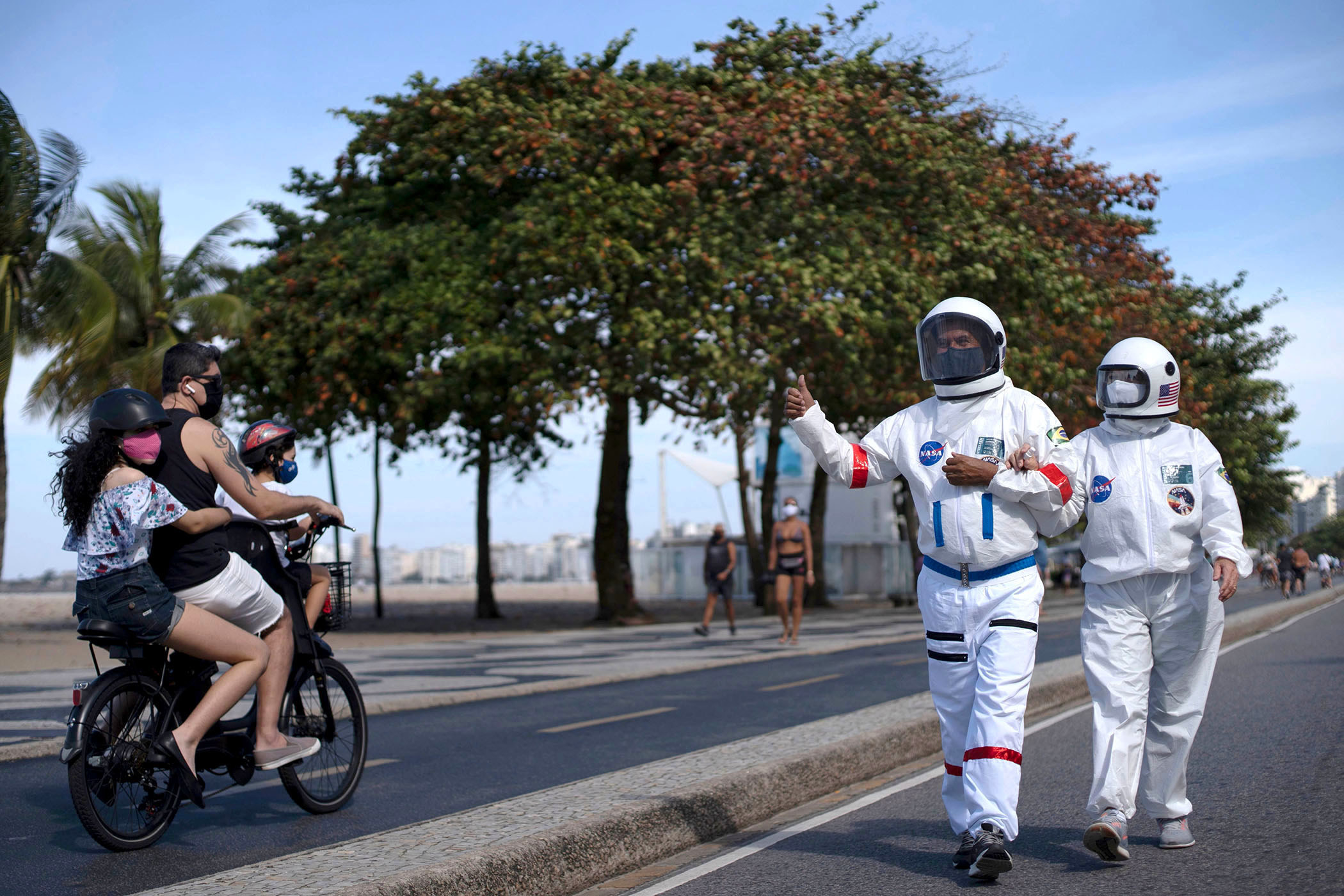 A man and woman wear spacesuits and face masks; the man gives a thumbs up to three people wearing face masks on a bicycle