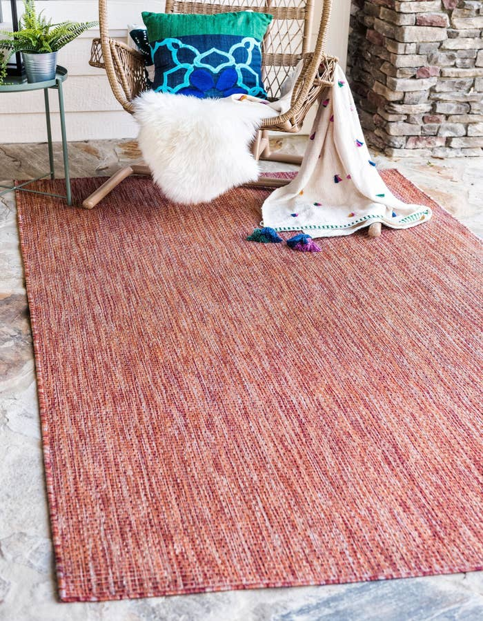 A rust-red color outdoor rug on the ground