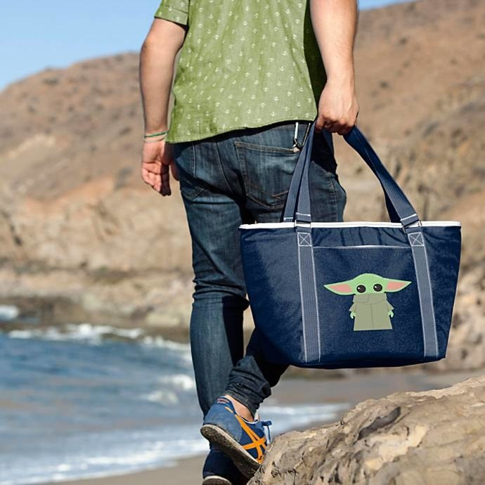 A model carrying the large navy tote with a cartoon Baby Yoda on it