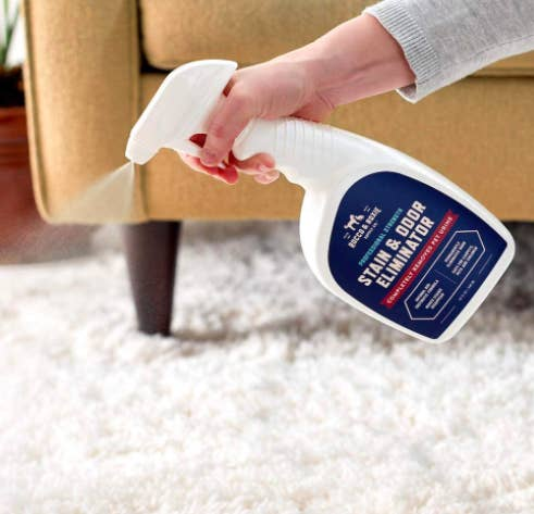 Hand spraying a white bottle of the stain and order eliminator