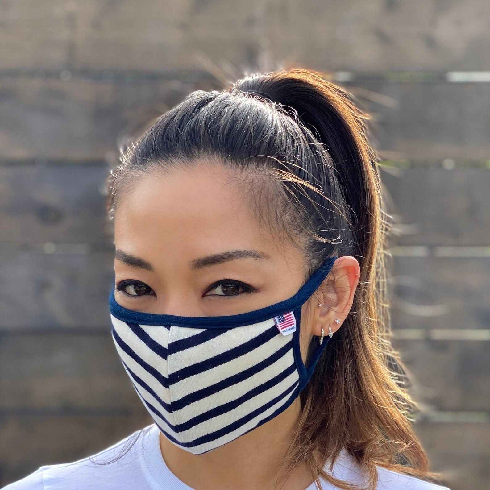 A model in a white and blue striped face mask