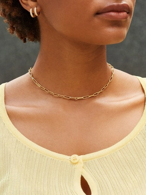 model with scoop yellow neckline and the small link gold necklace with a choker-like fit