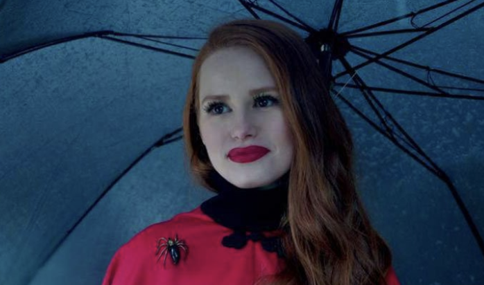 "Cheryl Blossom from ""Riverdale"" wearing a cape under an umbrella."