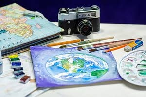 an art table with paint brushes, a camera, and a painting