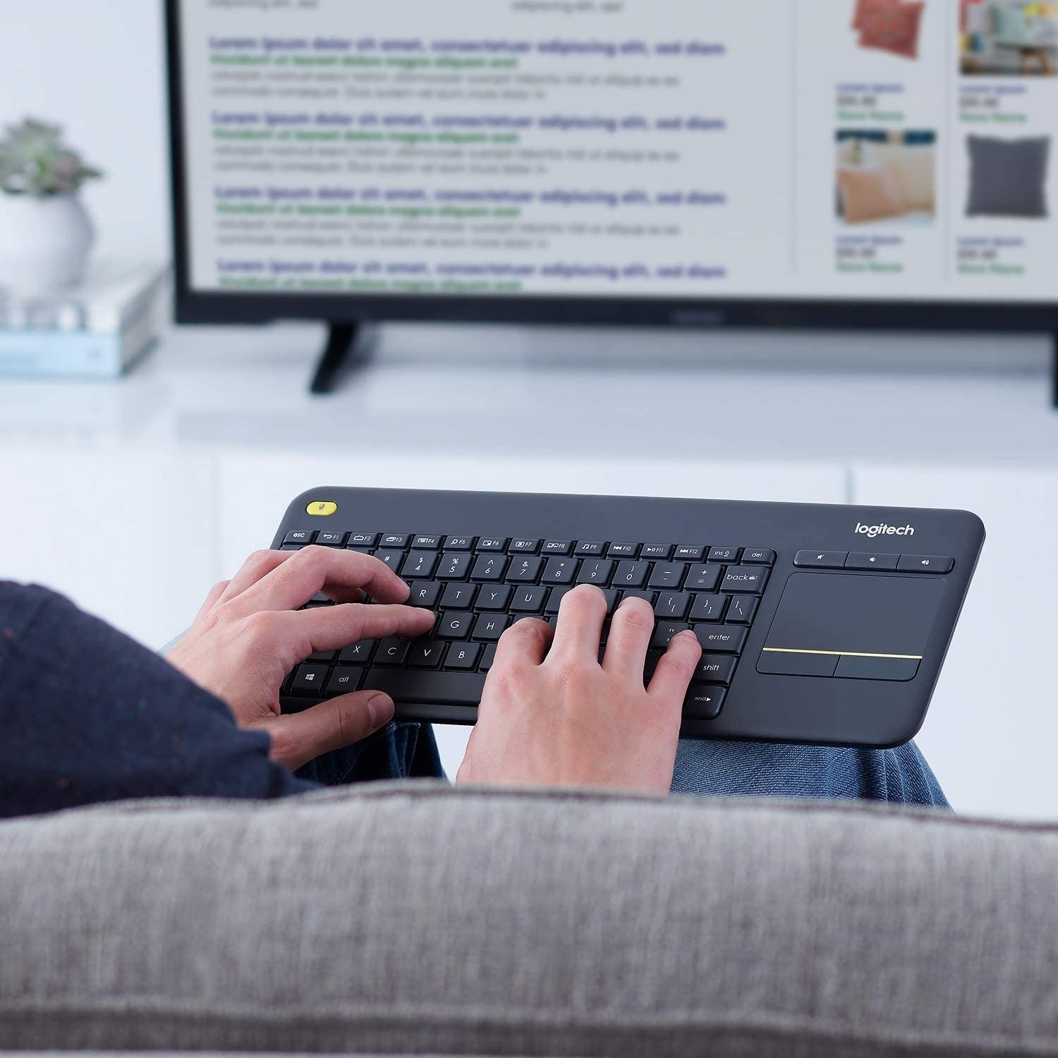A person typing on the keyboard in front of their TV