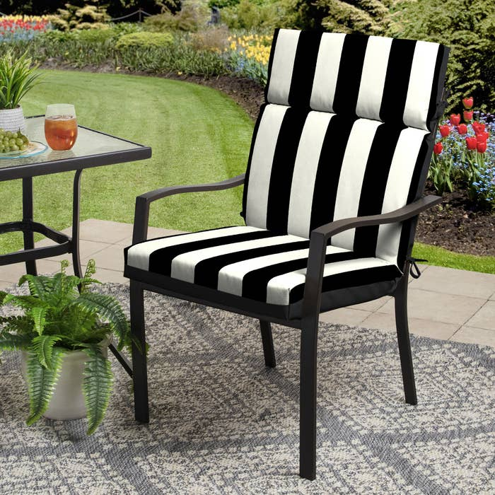 a black and white striped cushion on a black metal lawn chair