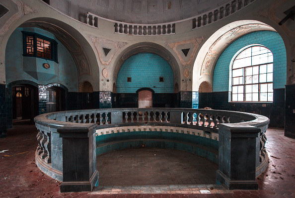 Decadent bath house that had been abandoned, bright turquoise tiles, round wall and red floor tiles
