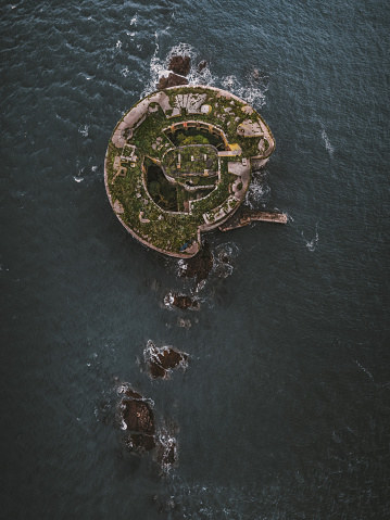aerial view of fort in the middle of the sea in Wales, greenery on top of fort