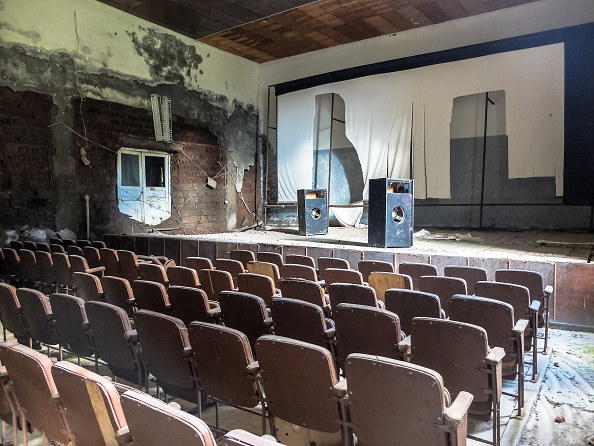 old theatre with ripped screen and decaying walls, empty seats