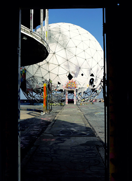 spherical white structure with graffiti and exposed base in a doorway