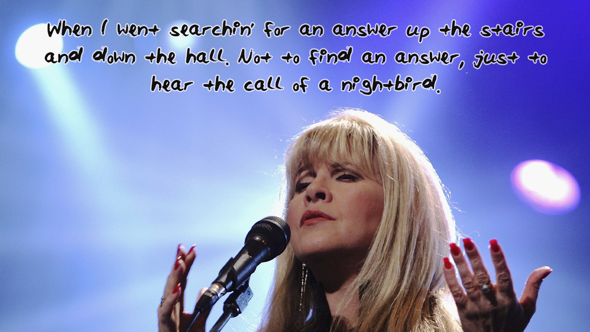 Close up of Stevie Nicks on stage with the lyrics when I went searching for an answer up the stairs and down the hall not to find an answer just to hear the call of a nightbird on top