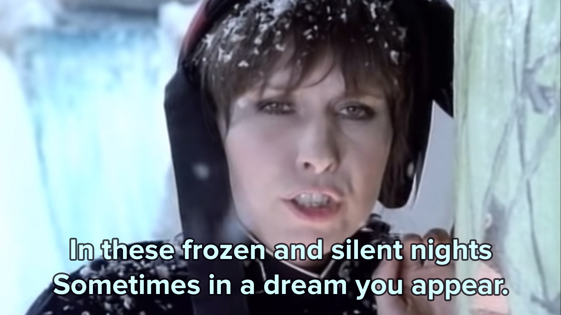 Chrissie Hynde of the Pretenders leans against a tree in snowy apparell in her music video for 2000 miles with the lyrics in those frozen and silent nights sometimes in a dream you appear on top