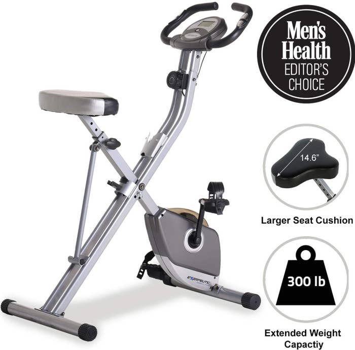 """The silvery bike, with text """"Men's Health editor's choice"""" larger seat cushion, 300 pound extended weight capacity"""